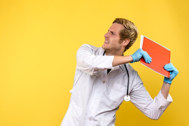 Widok z przodu mężczyzna lekarz posiadający analizy na żółtym tle ludzkiego wirusa medycznego zdrowia