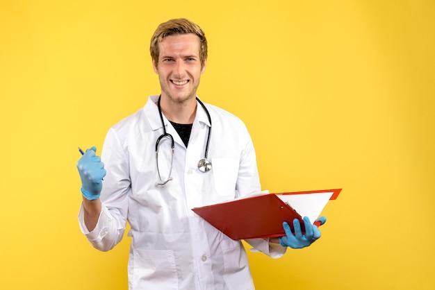 Widok z przodu mężczyzna lekarz posiadający plik z notatkami na żółtym biurku medyk ludzki wirus