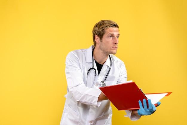 Widok z przodu mężczyzna lekarz posiadający plik z notatkami na żółtym tle medyczny medyczny wirus ludzki