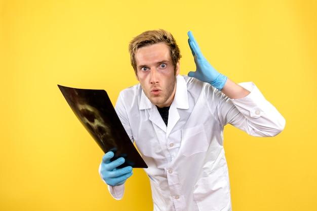 Widok z przodu mężczyzna lekarz posiadający prześwietlenie na żółtym tle lekarz covid higiena chirurgiczna