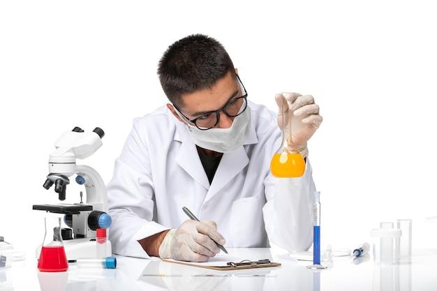 Widok z przodu mężczyzna lekarz w białym garniturze medycznym iz maską pracujący z roztworami na białej przestrzeni