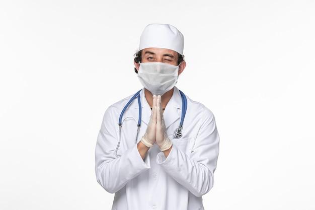 Widok z przodu mężczyzna lekarz w kombinezonie medycznym noszący sterylną maskę jako ochrona przed covid modląc się na chorobie pandemicznej wirusa koronawirusa białej ściany