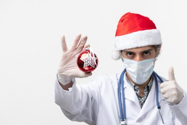 Widok z przodu mężczyzna lekarz w masce z zabawką na białej ścianie wirus covid zdrowia nowy rok