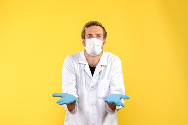 Widok z przodu mężczyzna lekarz zdezorientowany na żółtym tle pandemia pandemii zdrowia