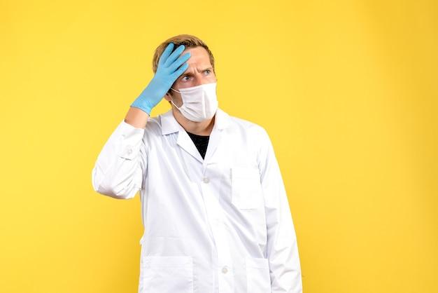 Widok z przodu mężczyzna lekarz zdezorientowany w masce na żółtym tle pandemia zdrowia medycznego