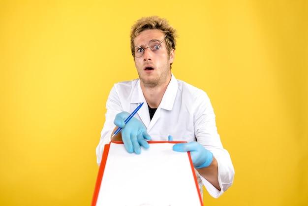 Widok z przodu mężczyzna lekarza z notatkami na żółtym tle zdrowia człowieka