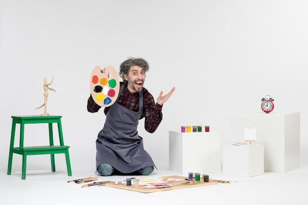 Widok z przodu mężczyzna malarz przygotowujący się do rysowania farbami na białym tle kolor mężczyzna obraz rysunek artysta malarstwo sztuka