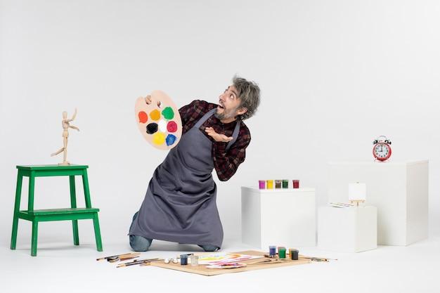 Widok z przodu mężczyzna malarz przygotowujący się do rysowania farbami na białym tle kolor rysunek artysta malarstwo sztuka obraz mężczyzna
