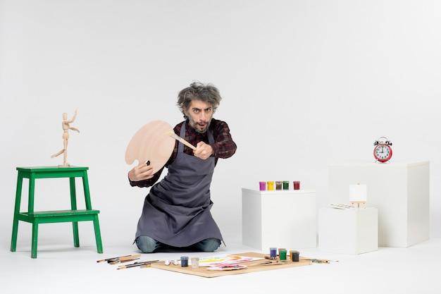 Widok z przodu mężczyzna malarz przygotowujący się do rysowania farbami na białym tle mężczyzna sztuka obraz artysta rysunek malowanie kolor