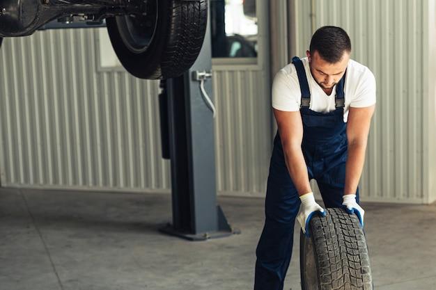 Widok z przodu mężczyzna mechanik pchanie koła