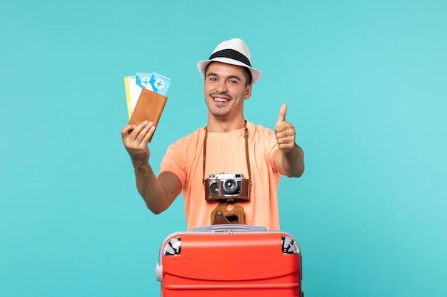 Widok z przodu mężczyzna na wakacjach, trzymający bilety na niebieskiej podłodze, podróż wakacyjna podróż samolotem morskim