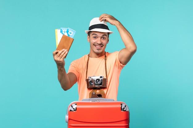 Widok z przodu mężczyzna na wakacjach trzymający bilety uśmiechający się na niebiesko