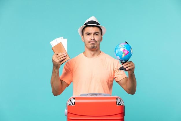 Widok z przodu mężczyzna na wakacjach, trzymający małą kulę ziemską i bilety na jasnoniebieskim kolorze