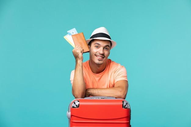 Widok z przodu mężczyzna na wakacjach trzymający swoje bilety na jasnoniebieskim kolorze