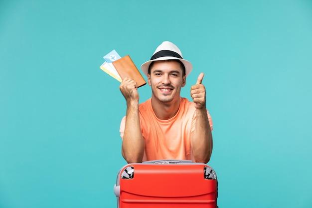 Widok z przodu mężczyzna na wakacjach trzymający swoje bilety na niebiesko