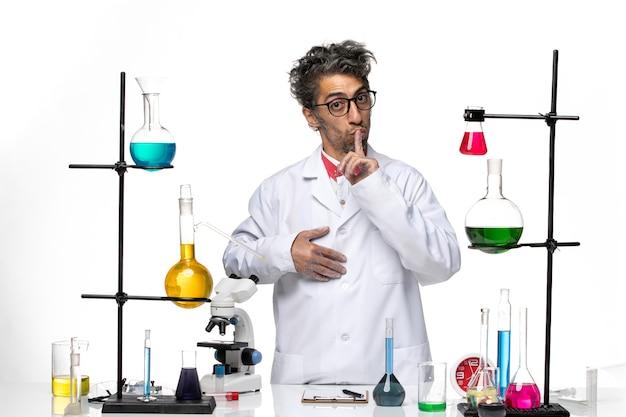 Widok z przodu mężczyzna naukowiec proszący o milczenie na białym tle laboratorium covid- chemia wirus nauki zdrowie