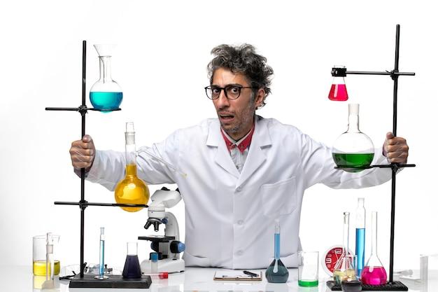 Widok z przodu mężczyzna naukowiec w białym garniturze medycznym, patrząc uważnie