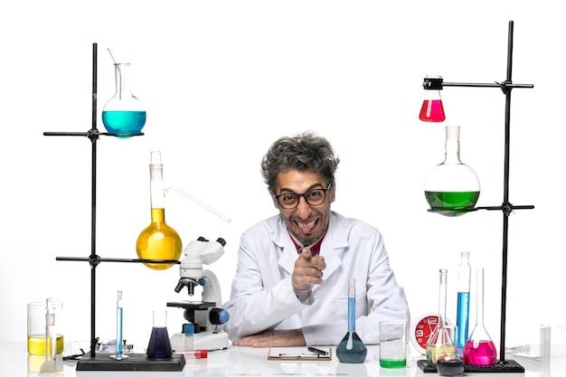 Widok z przodu mężczyzna naukowiec w białym garniturze medycznym siedzi przed stołem z roztworami