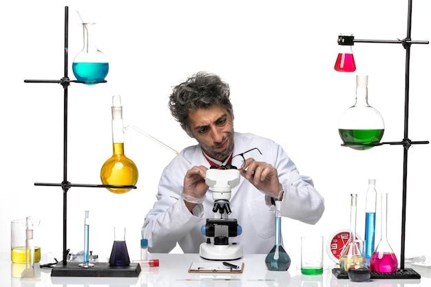 Widok z przodu mężczyzna naukowiec w białym garniturze medycznym, sprawdzanie jego okularów przeciwsłonecznych