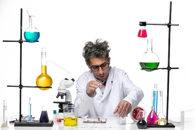 Widok z przodu mężczyzna naukowiec w garniturze medycznym pracujący z rozwiązaniami