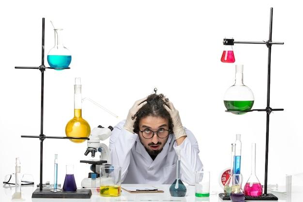 Widok z przodu mężczyzna naukowiec w garniturze medycznym siedzi i czuje się zmęczony na białej przestrzeni