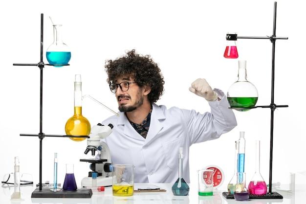 Widok z przodu mężczyzna naukowiec w kombinezonie medycznym, siedzący z roztworami i mikroskopem na jasnobiałej przestrzeni