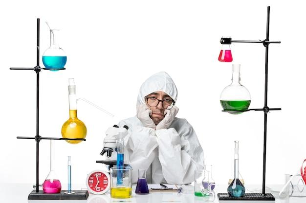 Widok z przodu mężczyzna naukowiec w specjalnym kombinezonie ochronnym siedzący wokół biurka z znudzonymi rozwiązaniami