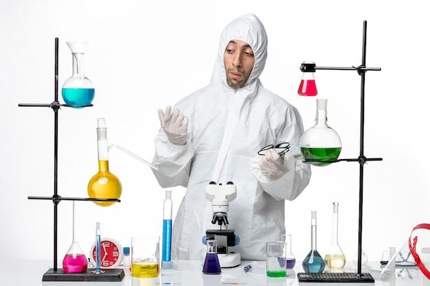 Widok z przodu mężczyzna naukowiec w specjalnym kombinezonie ochronnym, stojący wokół stołu z rozwiązaniami