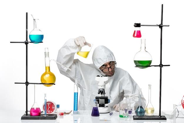 Widok z przodu mężczyzna naukowiec w specjalnym kombinezonie ochronnym, trzymając kolbę z roztworem