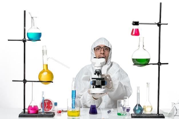 Widok z przodu mężczyzna naukowiec w specjalnym kombinezonie ochronnym, trzymając mikroskop
