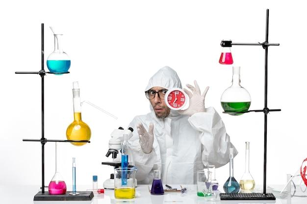Widok z przodu mężczyzna naukowiec w specjalnym kostiumie ochronnym, trzymając czerwone zegary