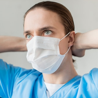 Widok z przodu mężczyzna pielęgniarka z maską medyczną