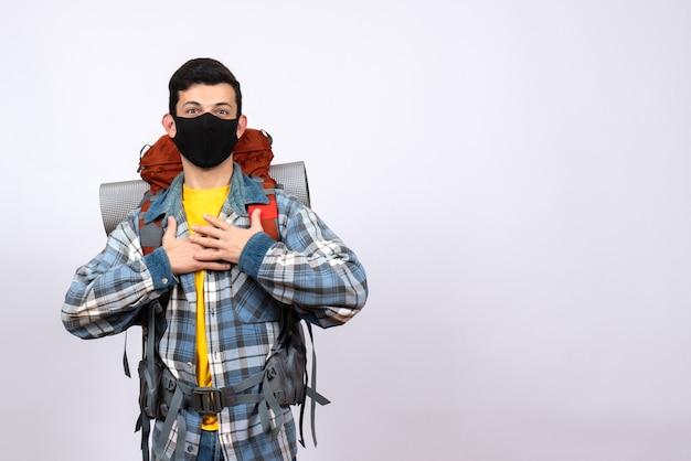 Widok z przodu mężczyzna podróżujący z plecakiem i maską kładący ręce na piersi