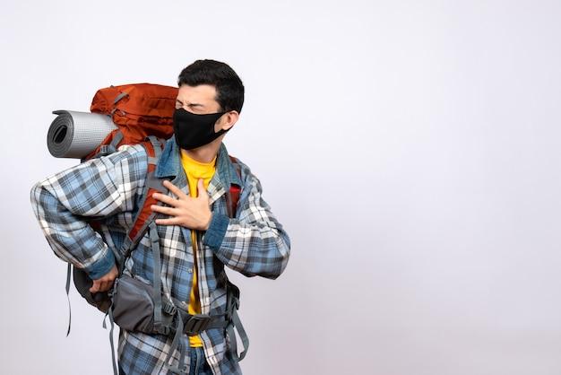Widok z przodu mężczyzna podróżujący z plecakiem i maską trzymający klatkę piersiową z bólem