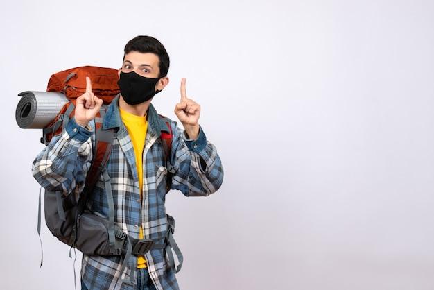 Widok z przodu mężczyzna podróżujący z plecakiem i maską, wskazując palcami w górę