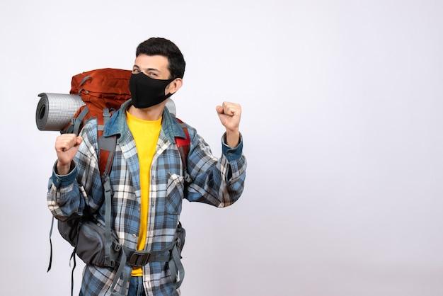 Widok z przodu mężczyzna podróżujący z plecakiem i maską wyrażającą swoje uczucia