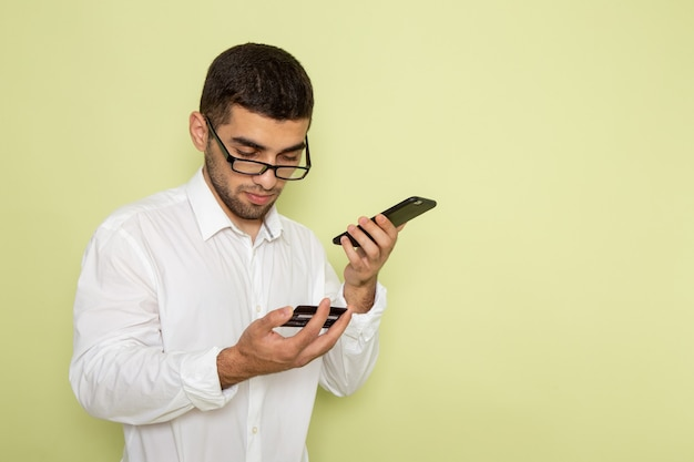 Widok z przodu mężczyzna pracownik biurowy w białej koszuli, trzymając i używając swojego telefonu na jasnozielonej ścianie