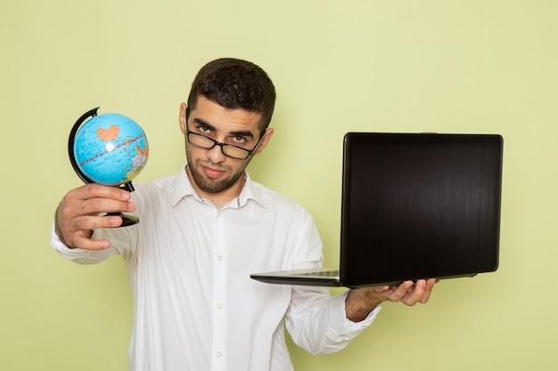Widok z przodu mężczyzna pracownik biurowy w białej koszuli, trzymając jego laptopa i kula ziemska na zielonej ścianie