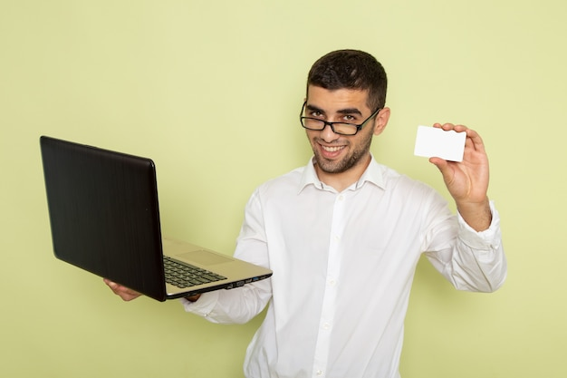 Widok z przodu mężczyzna pracownik biurowy w białej koszuli, trzymając laptopa i kartę na zielonej ścianie