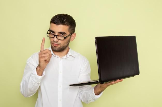 Widok z przodu mężczyzna pracownik biurowy w białej koszuli, trzymając laptopa na zielonej ścianie