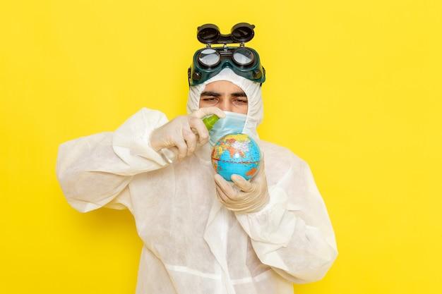 Widok z przodu mężczyzna pracownik naukowy w specjalnym garniturze trzymający mały okrągły glob rozpylający go na żółtej powierzchni