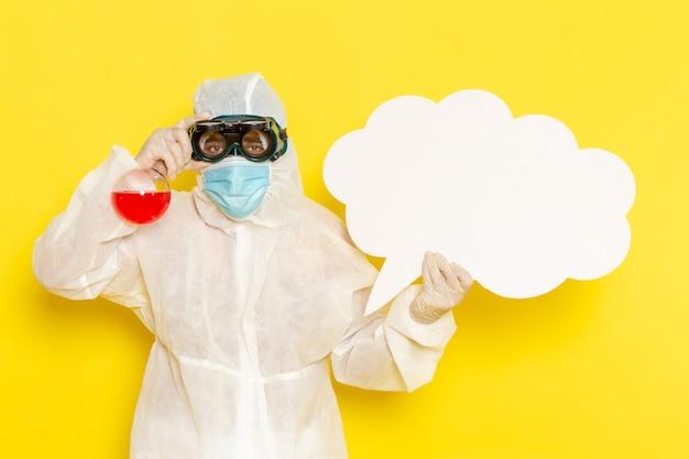 Widok z przodu mężczyzna pracownik naukowy w specjalnym kombinezonie ochronnym, trzymając kolbę z czerwonym roztworem i dużym białym znakiem na jasnożółtym biurku
