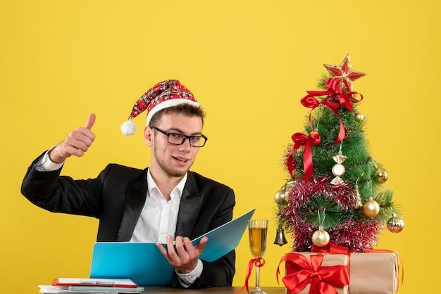 Widok z przodu mężczyzna pracownik siedzi i czyta dokumenty na żółto