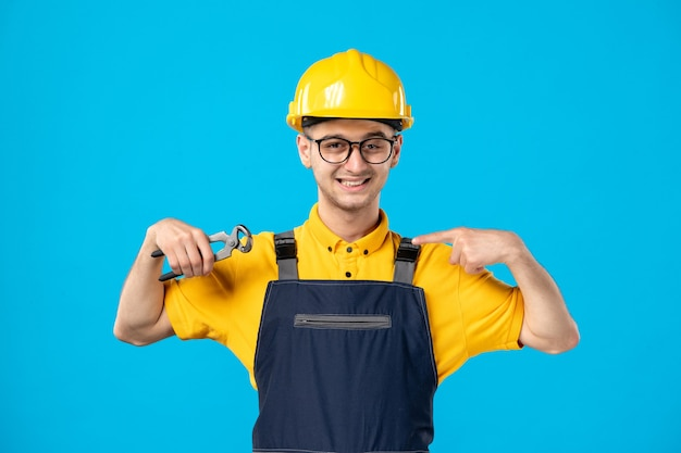 Widok z przodu mężczyzna robotnik w żółtym mundurze z szczypcami na niebiesko