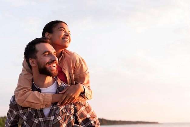 Widok z przodu mężczyzna trzyma swoją dziewczynę na plecach z miejsca na kopię