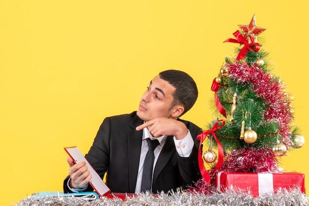 Widok z przodu mężczyzna w garniturze siedzi przy stole patrząc na prawo trzymającego dokument święta drzewo i prezenty