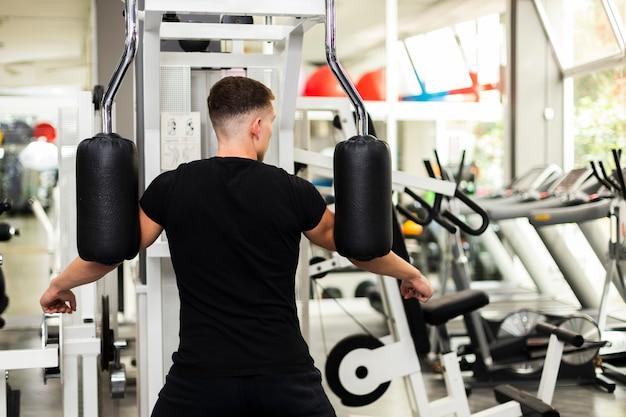 Widok z przodu mężczyzna w siłowni, ćwiczenia ramion