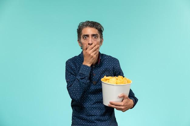 Widok z przodu mężczyzna w średnim wieku trzymając kosz z cipsami i oglądając film na niebieskiej powierzchni