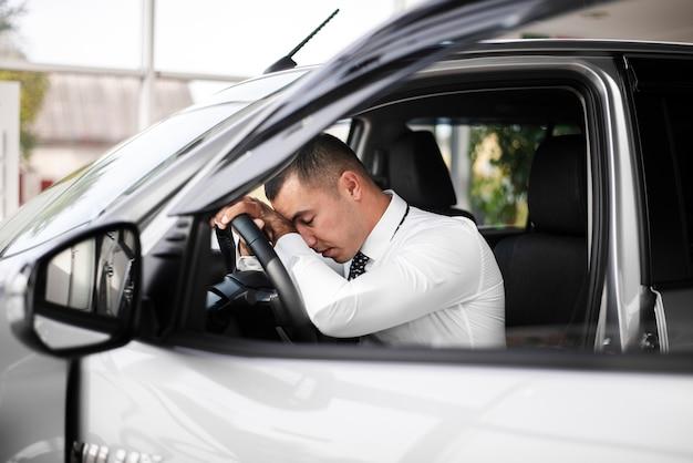 Widok z przodu mężczyzna z głową opartą na kierownicy koła