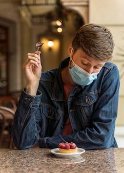 Widok z przodu mężczyzna z maską ciesząc się ciastem